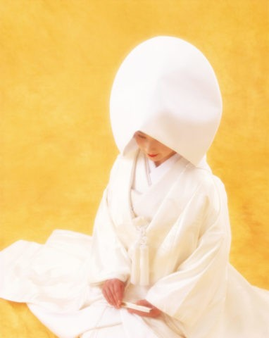 S 黄バックで座っている綿帽子の花嫁
