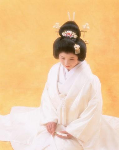 黄バックで座っている白無垢の花嫁
