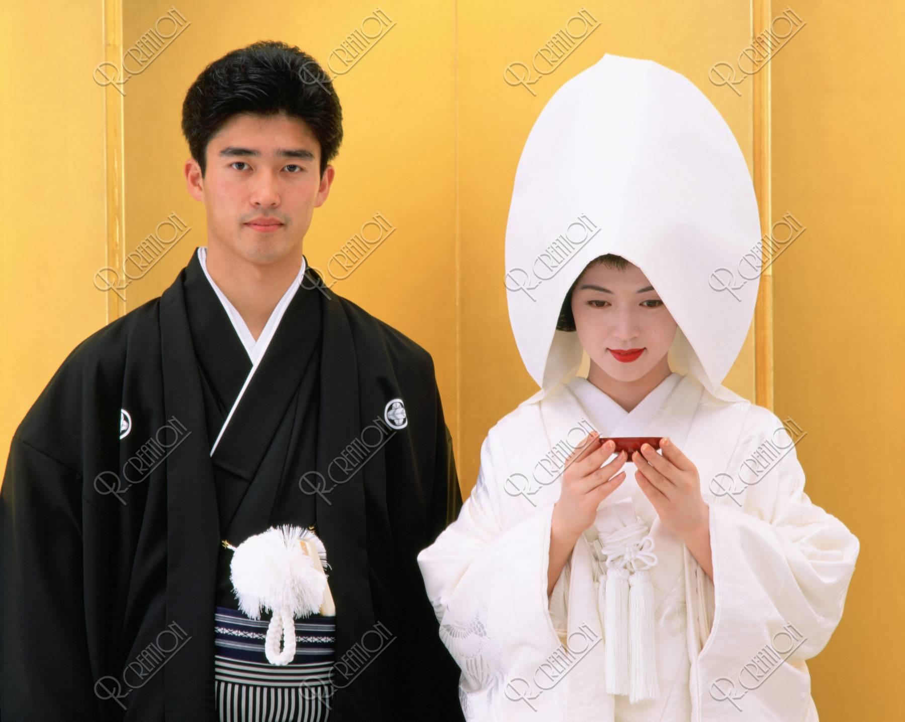 綿帽子で盃を持つ花嫁と花婿