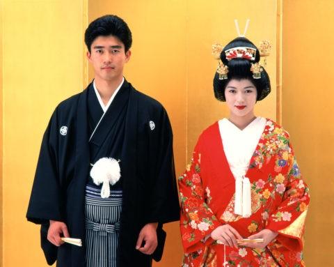 金屏風の前の和装の花嫁と花婿
