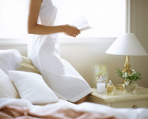寝室で本を読む女性