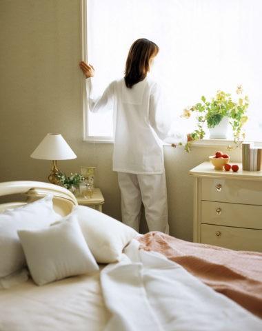 寝室で窓の外を見る女性