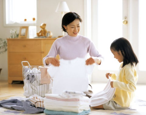 洗濯物をたたむ母と娘