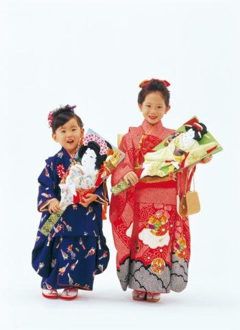 羽子板を持つ三歳と七歳の女の子