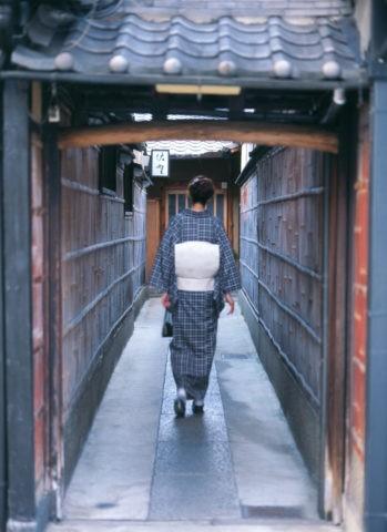 路地を歩く和服の女性