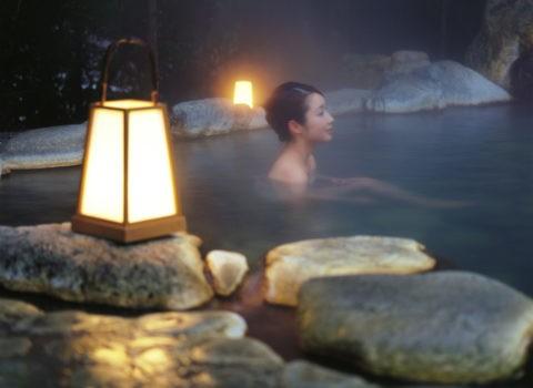行燈と露天風呂の女性