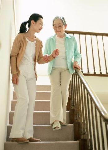 階段で介護する女性
