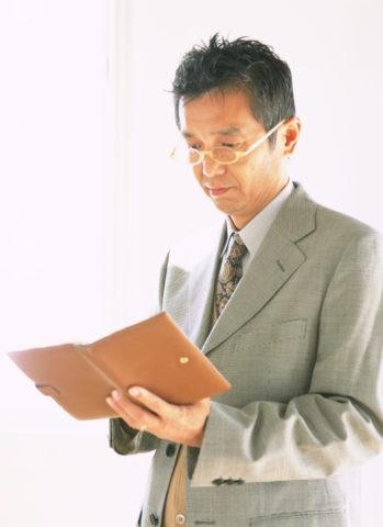 手帳を見るウオームビズの男性