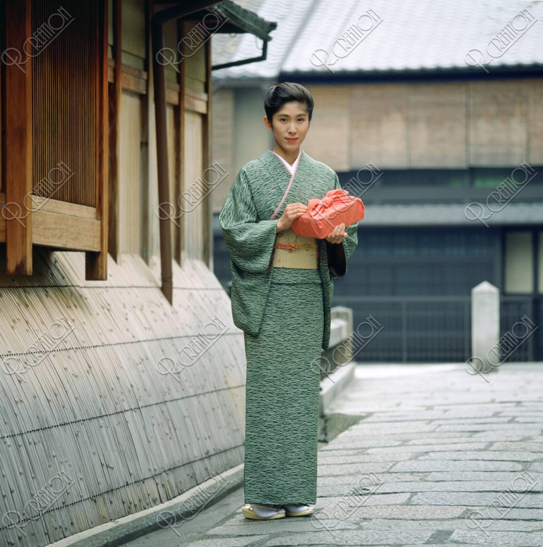 風呂敷包みを持つ和服の女性