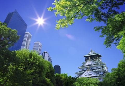 太陽光の射す大阪城とビジネスパーク
