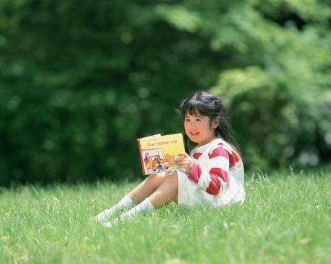 新緑の中で絵本を見る女の子