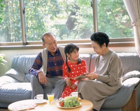 絵本を見る祖父母と孫