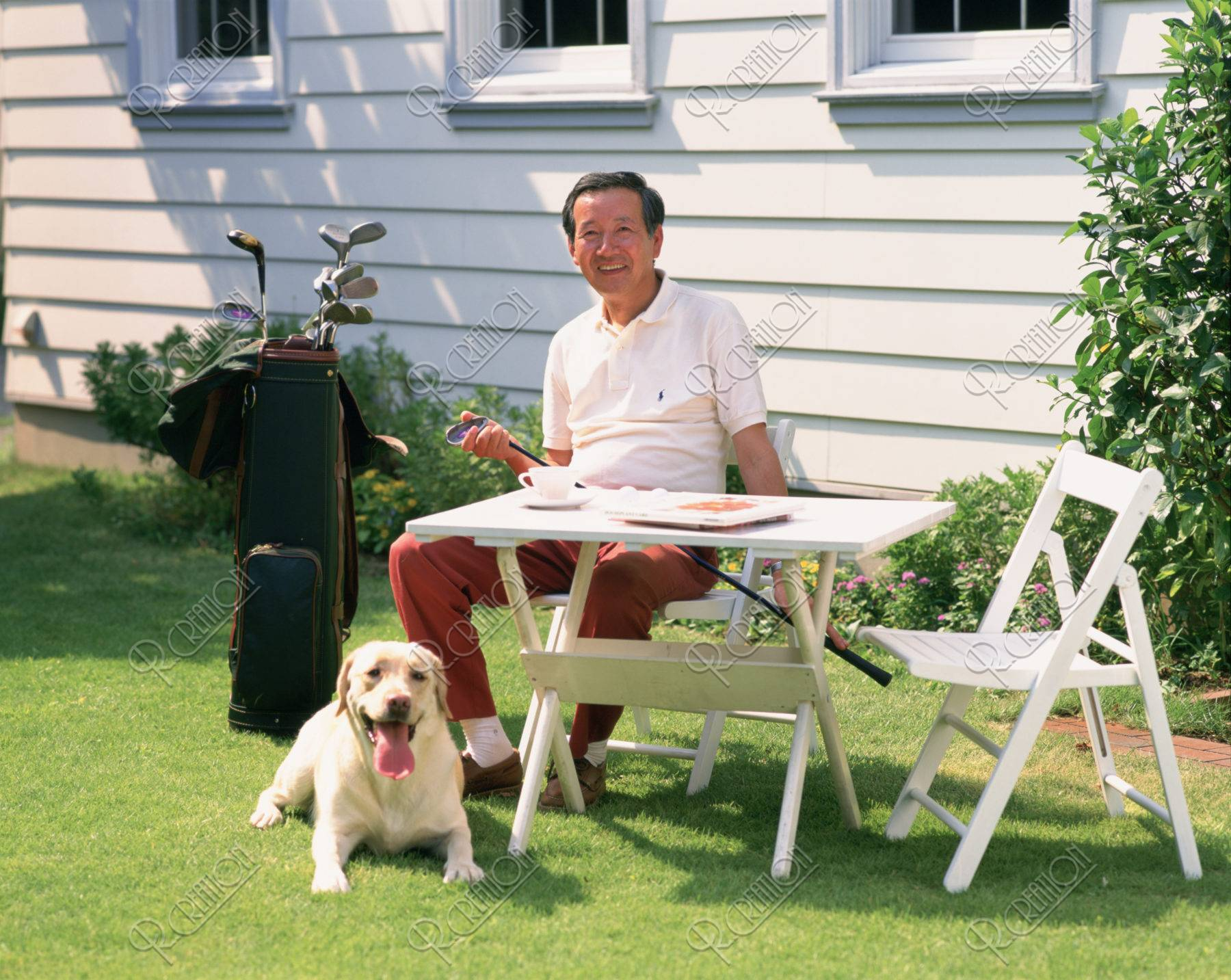熟年の男性と犬 庭