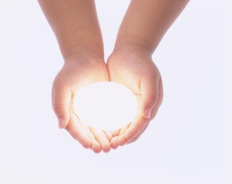 光る卵を持つ子供の手
