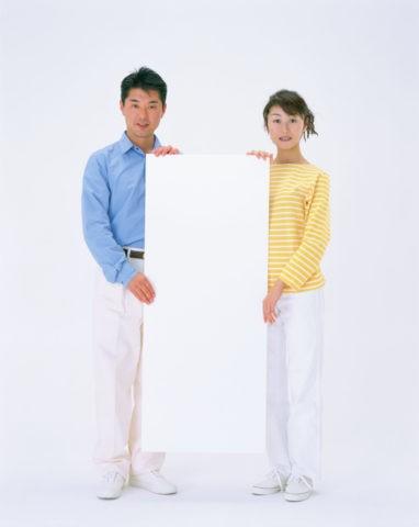 白いボードを持ったカップル