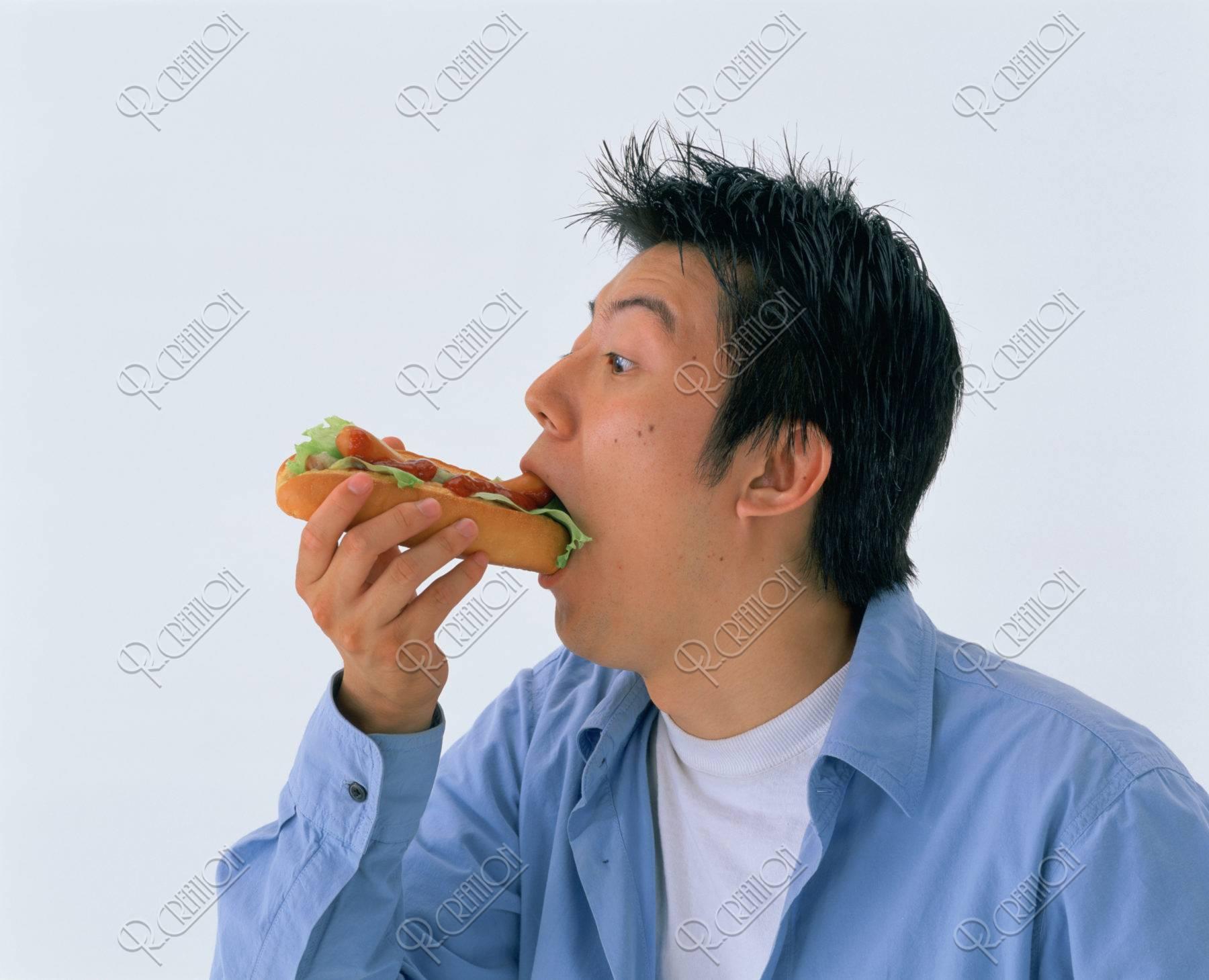 ホットドッグを食べる若者