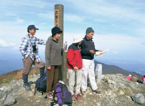 山頂に立つ中高年の4人