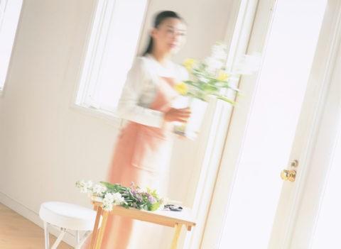 花瓶を持って移動する女性