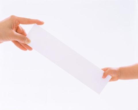 白いボードを渡す母と子の手