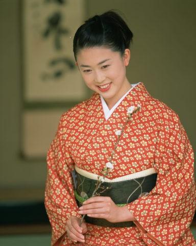 桜の枝と和服の女性