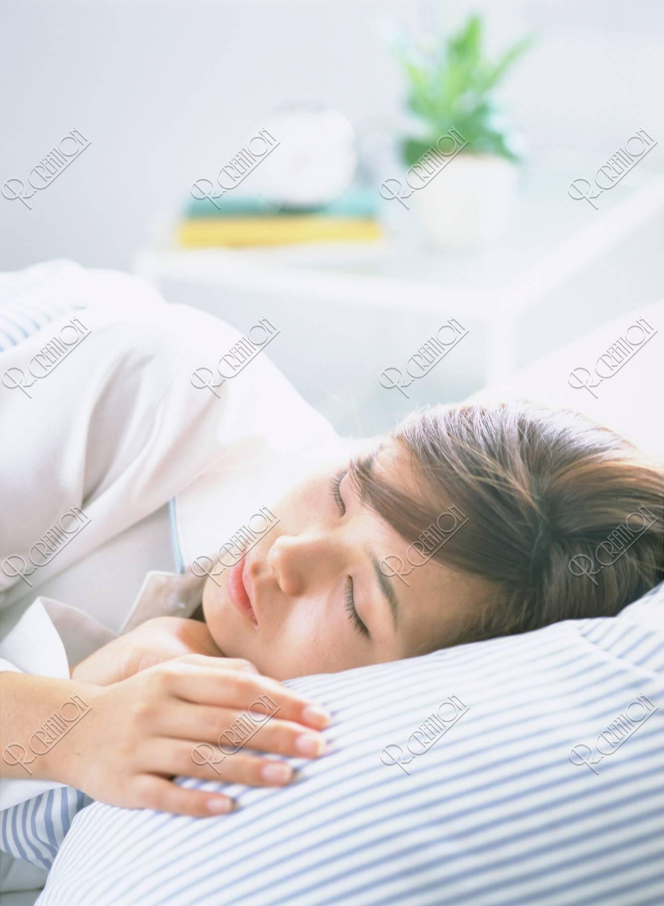 ベッドで寝る女性