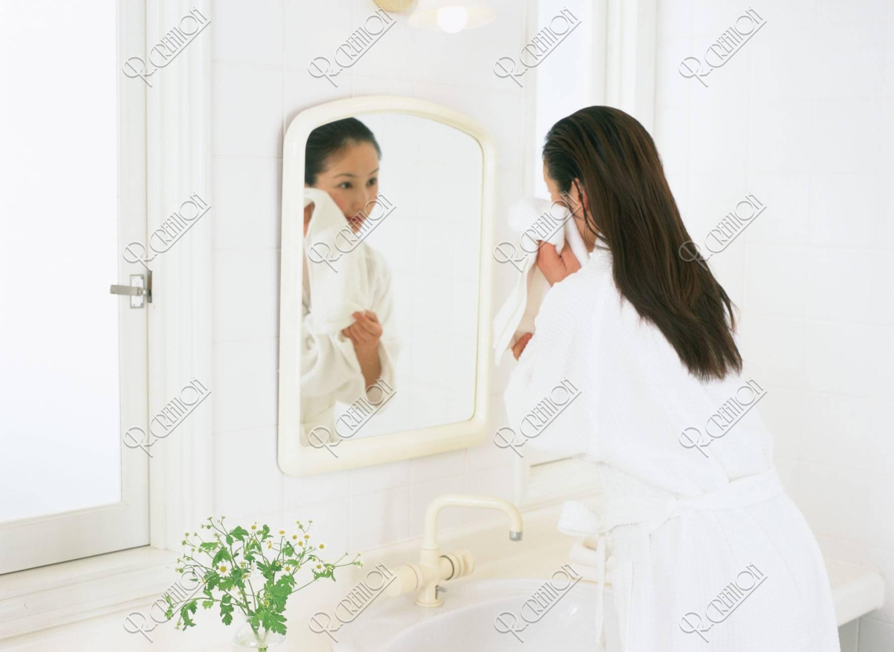 顔をふく女性