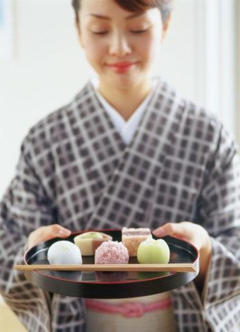 和菓子を持つ和服の女性