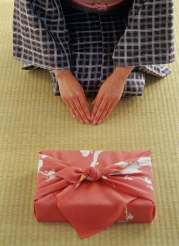 届け物と和服の女性