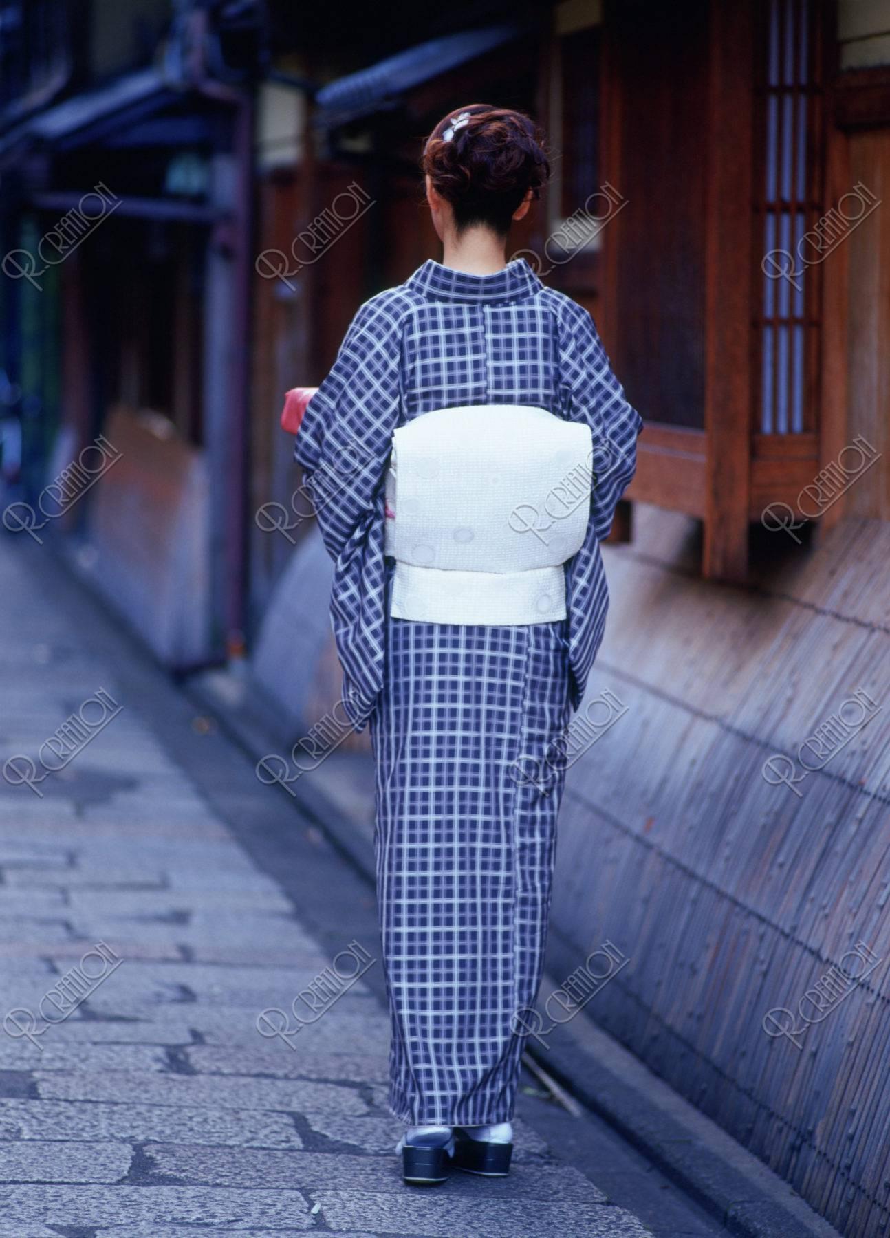 届けものを持つ和服の女性