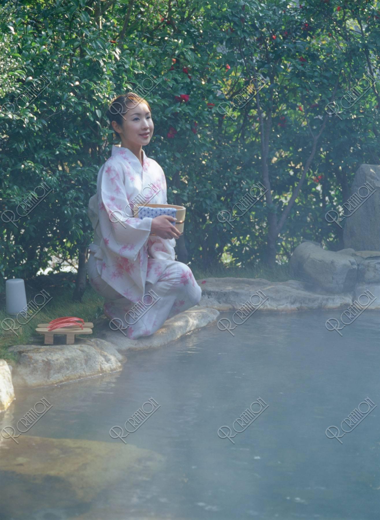 露天風呂で桶を持つ女性