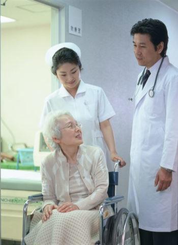 車椅子のお年寄りと看護士と医師