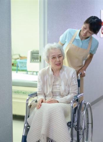 車椅子のお年寄りと介護人