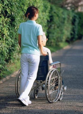 車椅子の老人と介護人