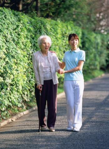 散歩する老人と介護人