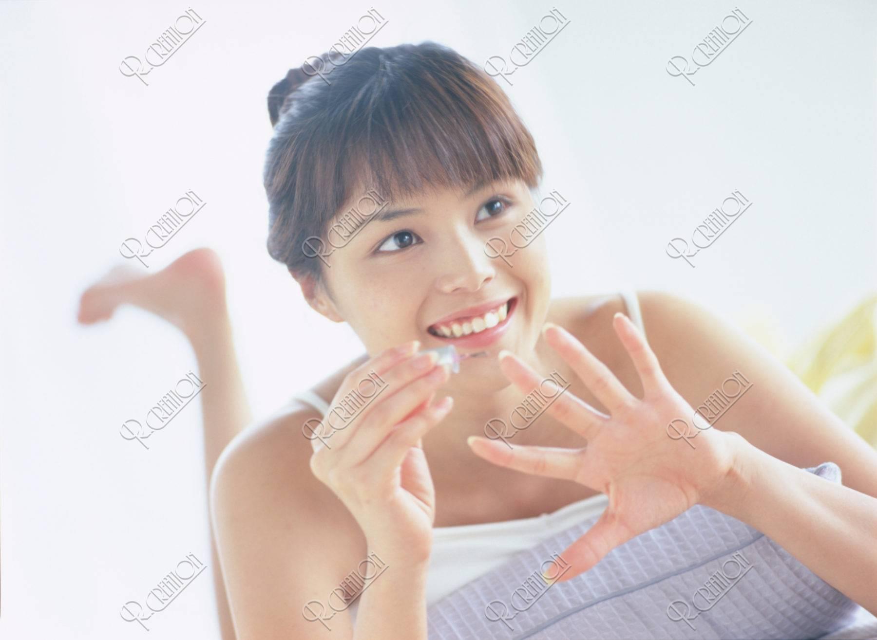 マニキュアをする女性