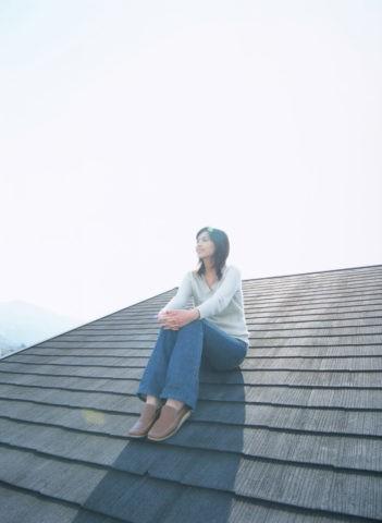屋根に座る女性