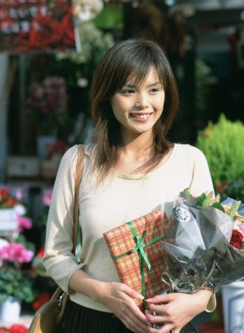 花とプレゼントを持つ女性