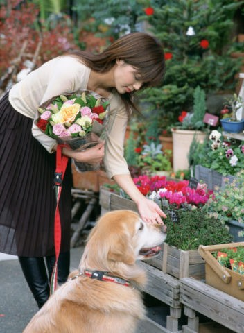 花屋の前の女性と犬