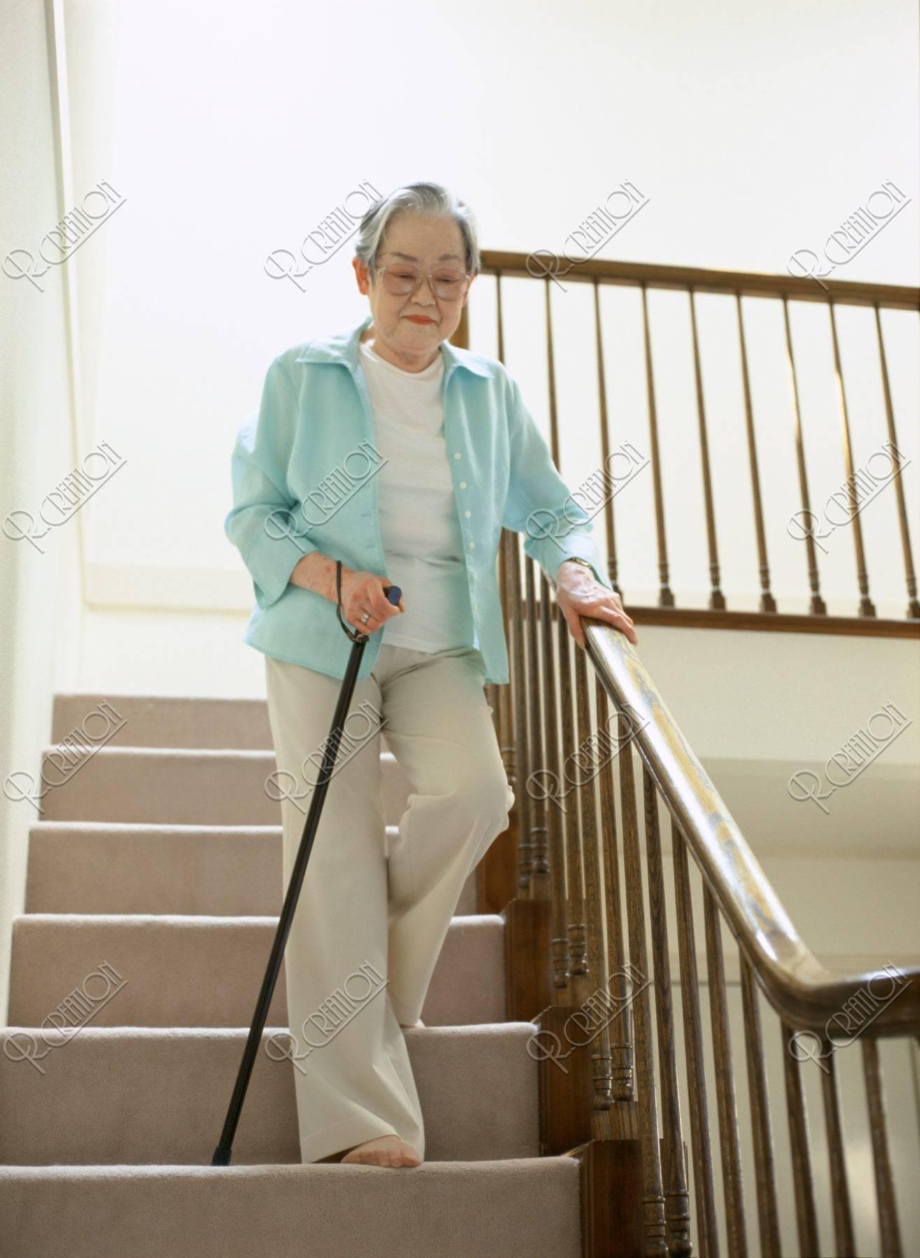 杖をついて階段を降りる老婦人