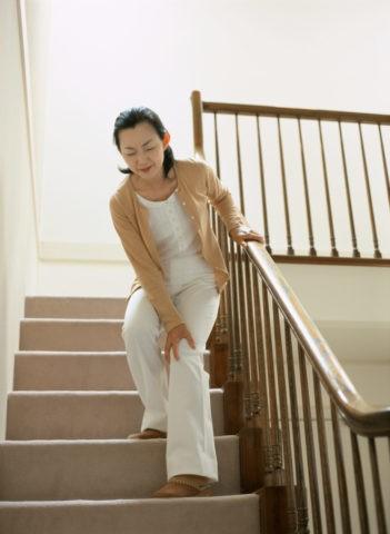 痛みをこらえて階段を降りる女性
