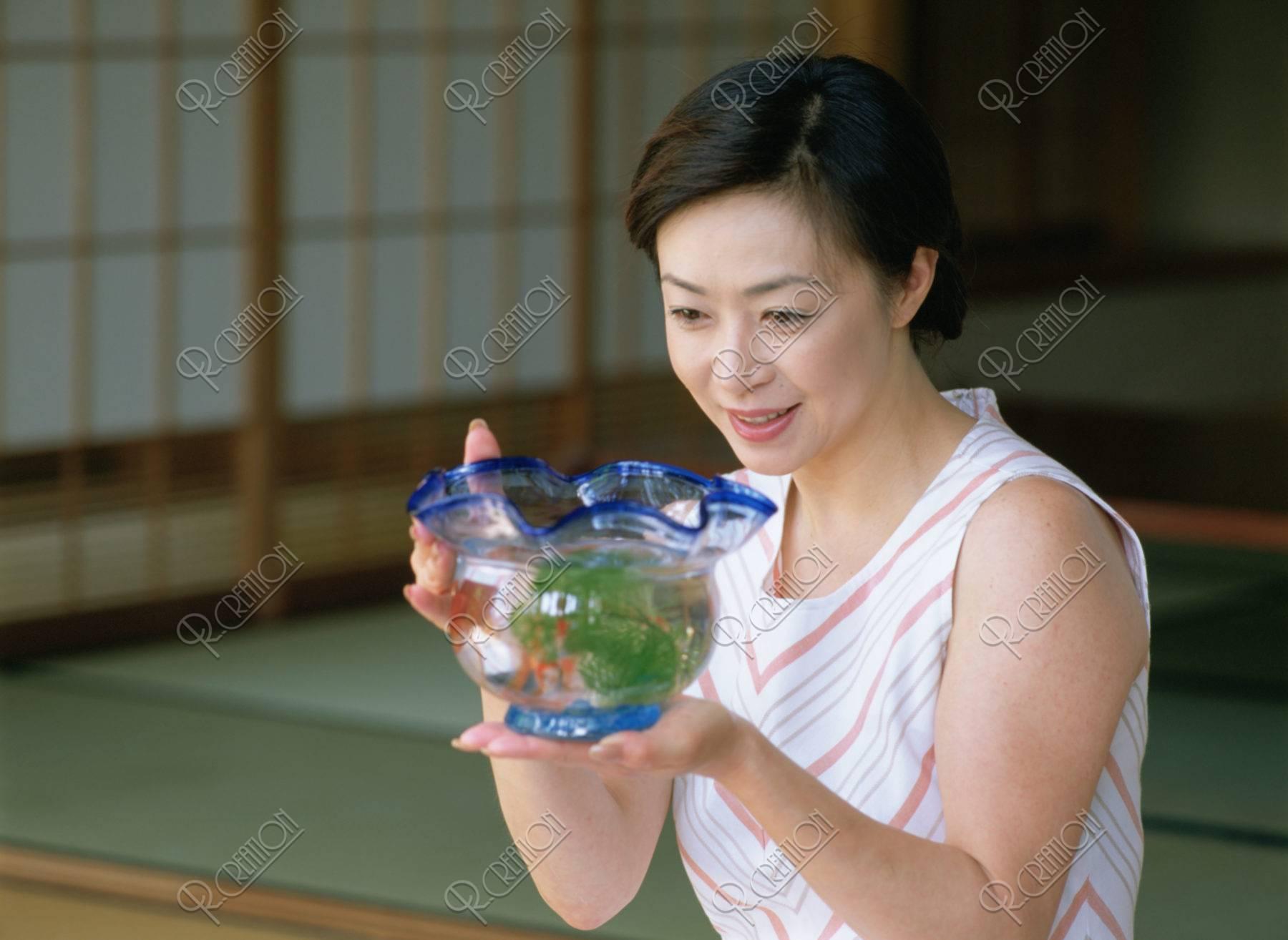 金魚鉢と熟年女性