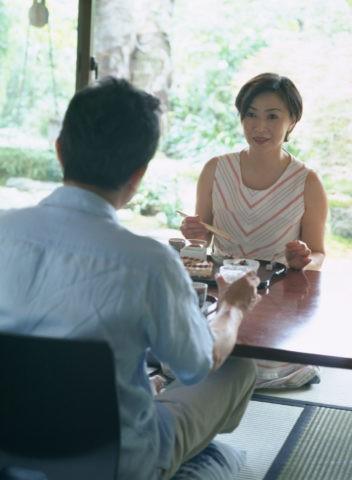 和室で食事する熟年夫婦