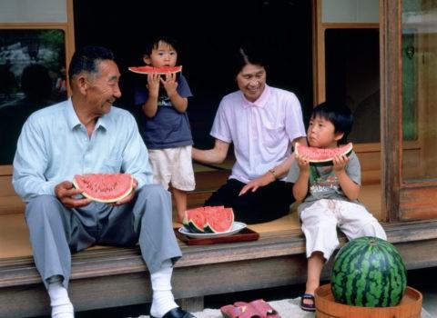 縁側でスイカを食べる祖父母と孫