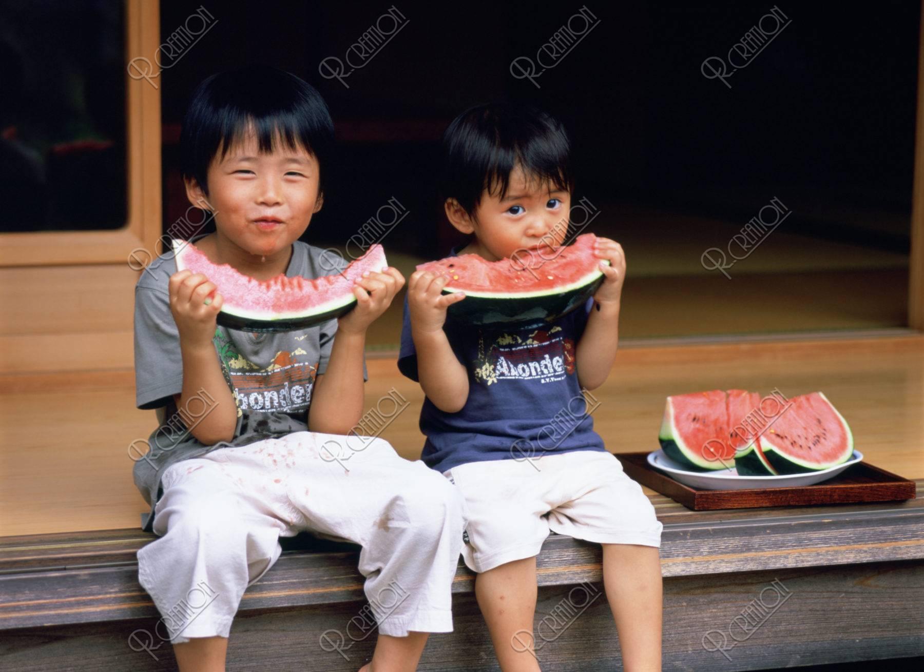 縁側でスイカを食べる兄弟