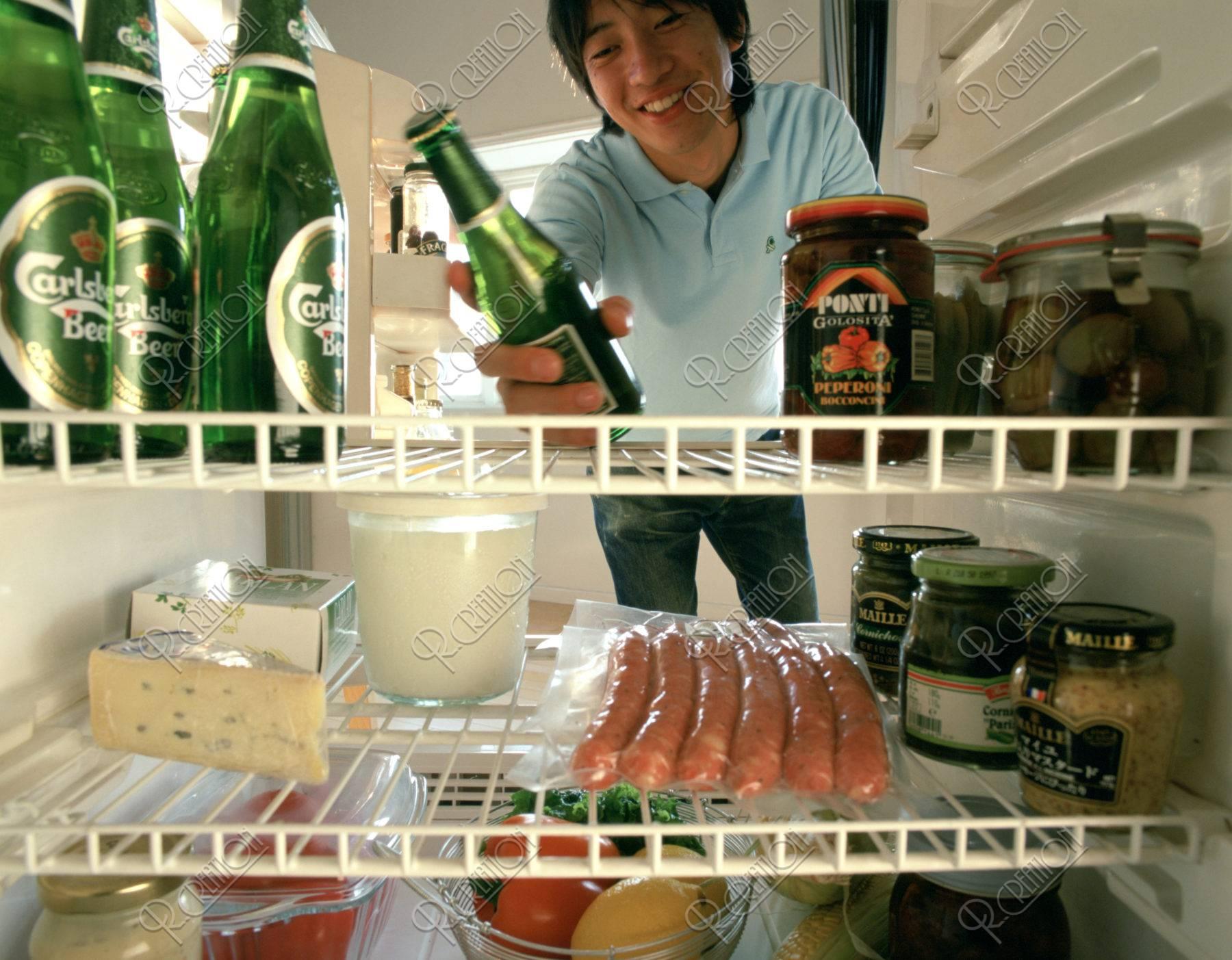 冷蔵庫からビールを取る男性
