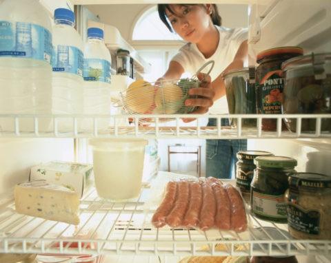 冷蔵庫から果物を取る女性