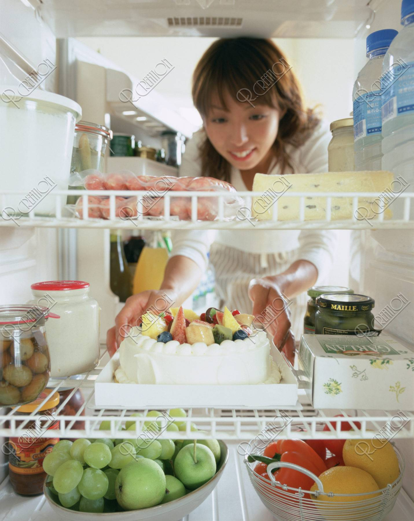 冷蔵庫からケーキを取る女性