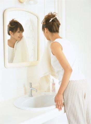 バスルームで鏡を見る女性