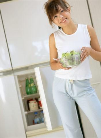 冷蔵庫をお尻で閉める女性