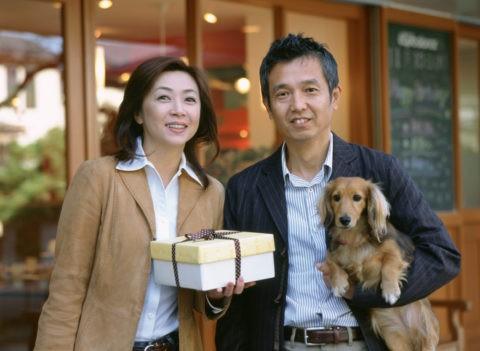 買い物の熟年カップルと犬